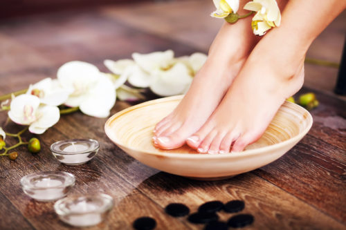 Closeup photo of a female feet at spa salon on pedicure procedure. Female legs in water decoration the flowers.